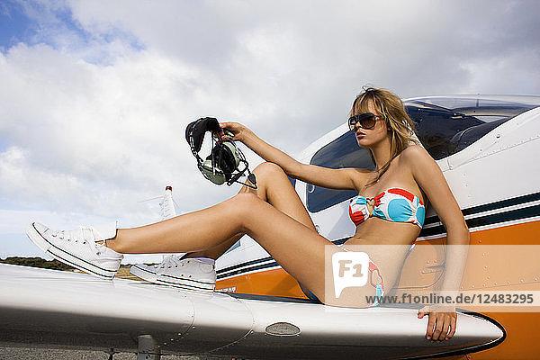 Model in bikini posing on airplane wing
