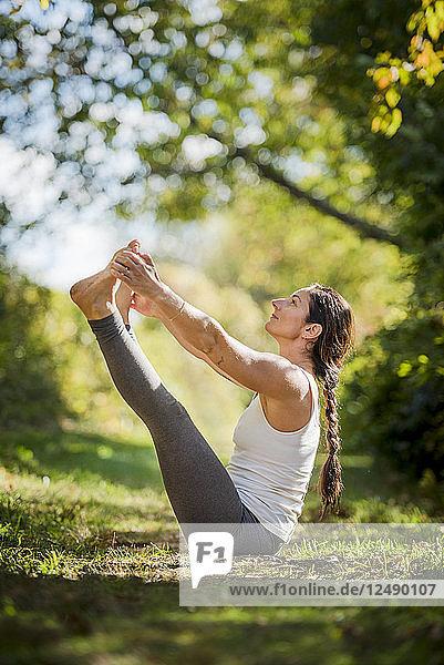 Woman Practicing Yoga On Grassy Landscape