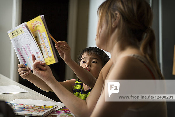 A Japanese boy studies Japanese homework in a kitchen as his mom helps him.