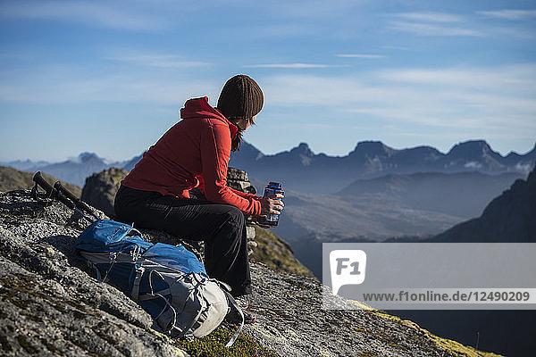 Female hiker takes a break and enjoys mountain views  Moskenes??y  Lofoten Islands  Norway