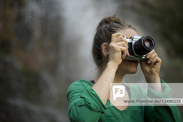 Woman Taking Picture In Camera While Hiking Near Mountain Waterfall