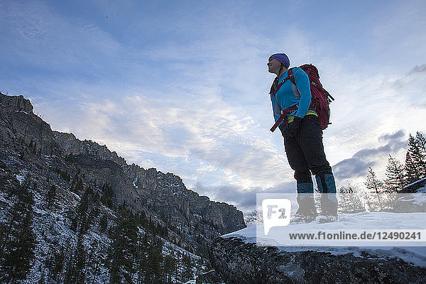 A woman hikes at dawn to an ice climb in Blodgett Canyon  Bitterroot Mountains  Montana.