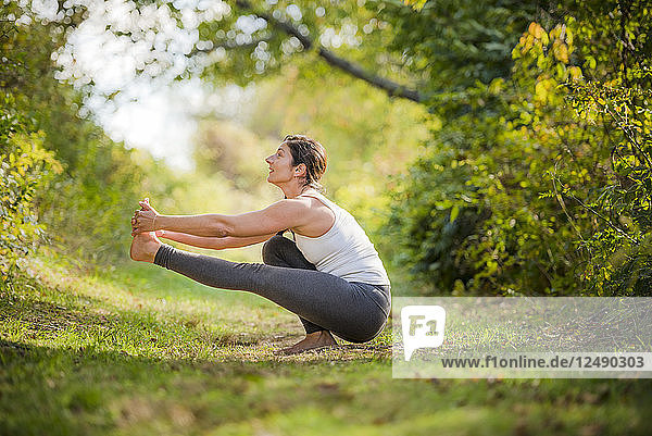 Woman Doing Stretching On Grassy Landscape
