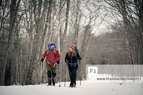 Two People Hiking In The Forest In Snow