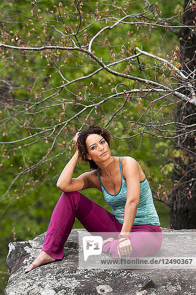 Woman Sitting On Rock Looking At Camera In Forest