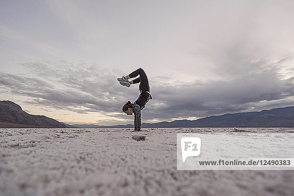 A Young Woman Does A Handstand On The Salt Flats In Badwater Basin  Death Valley National Park  California