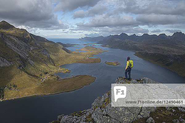 Female hiker takes in view over Selfjord from summit of Tverrfjellet  Lofoten Islands  Norway