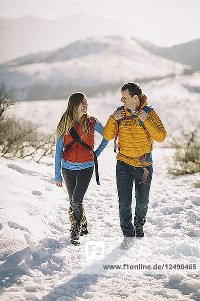 A young couple hikes in the wintry mountains.