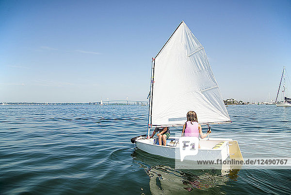 Young kids sailing a dinghy in Newport Harbor Young kids sailing a dinghy in Newport Harbor