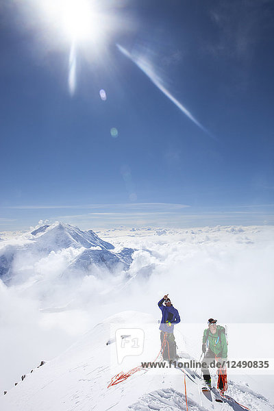 Climbers and rangers Dave Weber and Tom Ditolla are on a snow ridge of the West Rib high on Mount McKinley. Dave is pointing to the summit of McKinley  Mount Hunter is seen in the background. Mount McKinley or Denali is the highest mountain peak in North America  with a summit elevation of 20 237 feet (6 168 m) above sea level. At some 18 000 feet (5 500 m)  the base-to-peak rise is considered the largest of any mountain situated entirely above sea level. Measured by topographic prominence  it is the third most prominent peak after Mount Everest and Aconcagua. Located in the Alaska Range in the interior of the U.S. state of Alaska  McKinley is the centerpiece of Denali National Park and Preserve.'