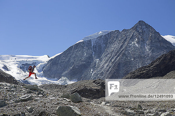 A male hiker is happily jumping in the air  in front of the Mont Blanc de Cheilon  a mountain at the end of the Val d'H?©r?©mence in the Swiss region of Valais. This is halfway the Haute Route  a popular alpine hike through France and Switzerland.