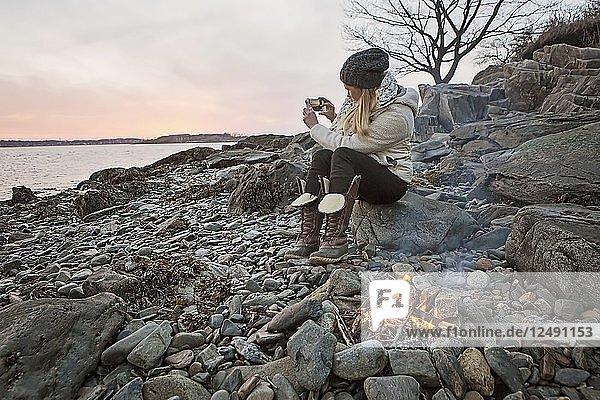 Woman Taking Picture Of River In Cellphone Along The Maine Coast