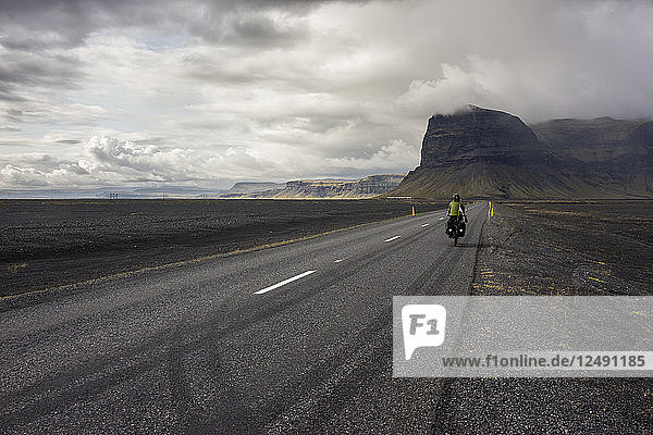 Woman riding touring bicycle on a straight road towards a mountain in a volcanic landscape.