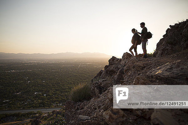 A young pregnant couple hikes above Salt Lake City  Utah at sunset.