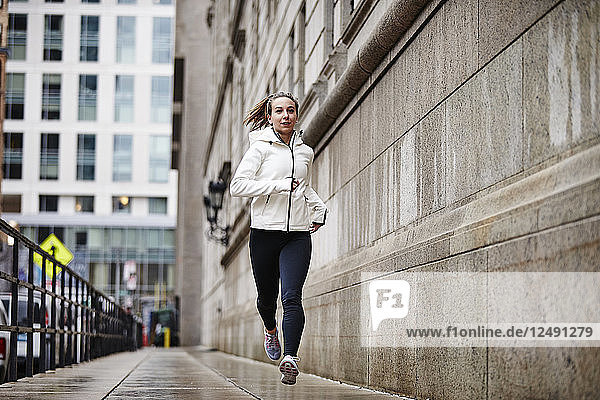 A Female Runner Running Through The Streets Of Boston