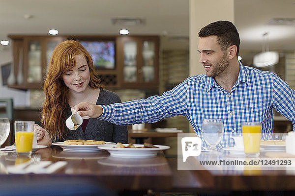 A lovely young couple enjoys snacks and fruit juice in a cafeteria.