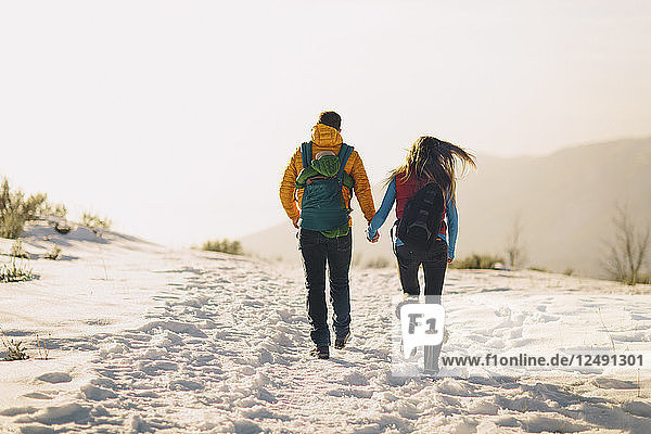 A young couple holds hands and hikes against a winter mountain scene and bright sunset.