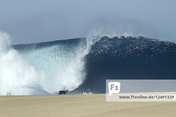 Surfing a big wave at the Banzai Pipeline  on Oahu's north shore.