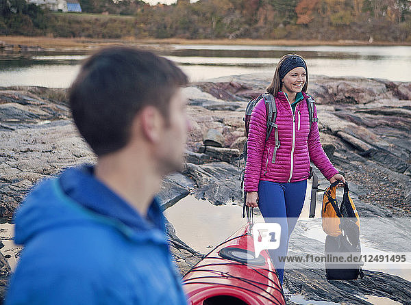 A young couple walk a kayak along the rocky shore of Maine.