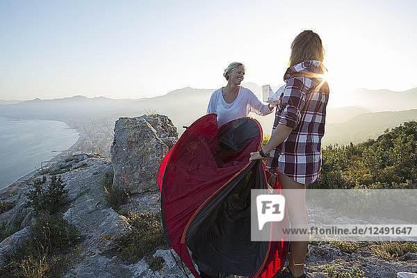 Mother and teenage daughter set up tent on hilltop above sea