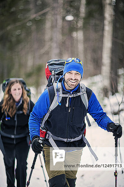 Two Hikers Trekking Through A Forest In Maine