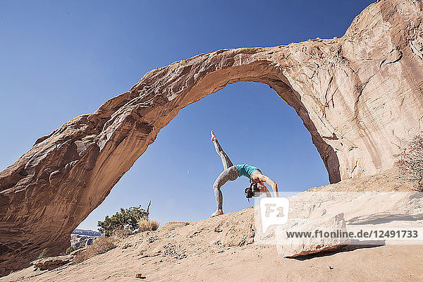 A Fit Young Woman Practices Yoga Under Corona Arch  Moab  Utah