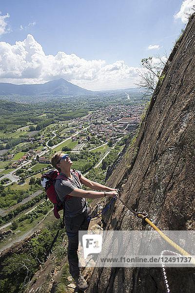 Young man ascends via ferrata  valley below