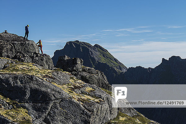 Two female hikers on summit on Nonstind mountain peak  Moskenes??y  Lofoten Islands  Norway