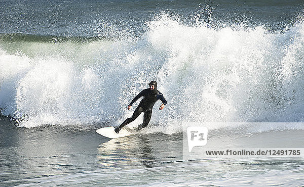 Surfer in wetsuit riding wave