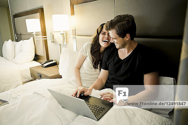 A Young Couple Sits In A Dallas Hotel Room Side By Side With A Laptop
