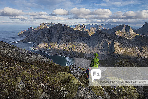 Female hiker takes in view over Bunes beach while hiking to Storskiva mountain peak  Moskenes??y  Lofoten Islands  Norway