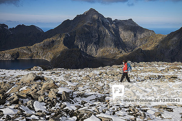 Female hiker on the rocky summit of Munken after a light autumn snow  Moskenes??y  Lofoten Islands  Norway