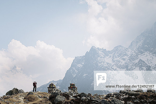 A trekker pauses to photograph the mountains of Nepal's Himalayas on the Everest Base Camp Trek.