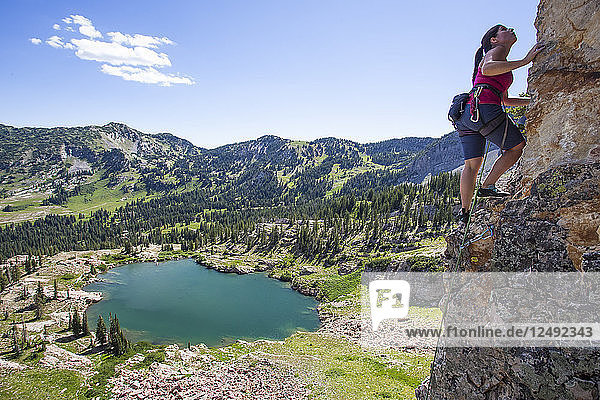 A women rock climbing stands on a big ledge and looks up at where she needs to go next.