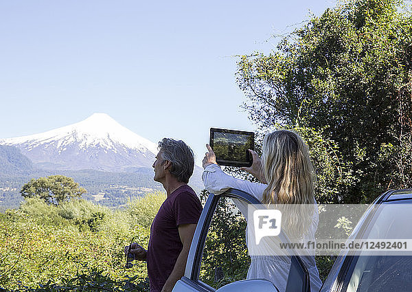 Woman takes photo of volcano with tablet from car  man watches