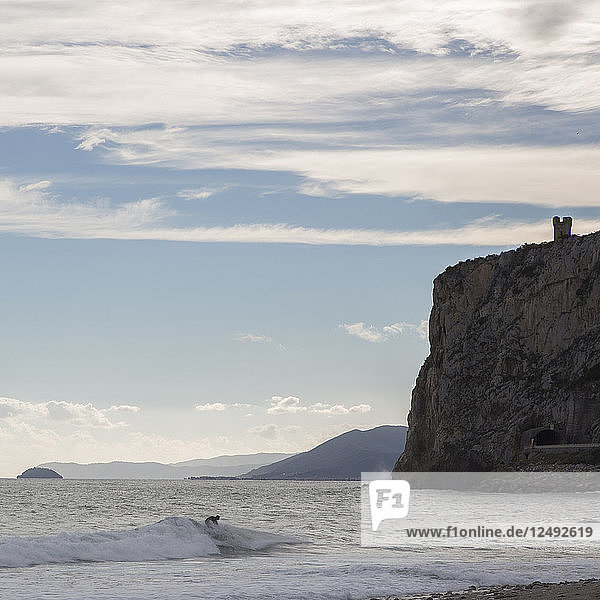 Surfers on beach and waves  Medieval tower on hill behind