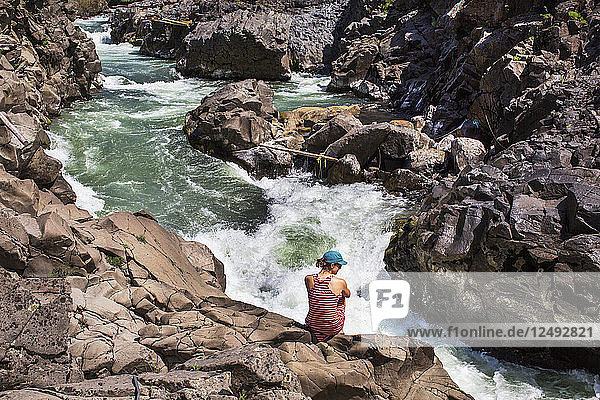 A woman in a red dress sits on rocks above a steep whitewater creek.