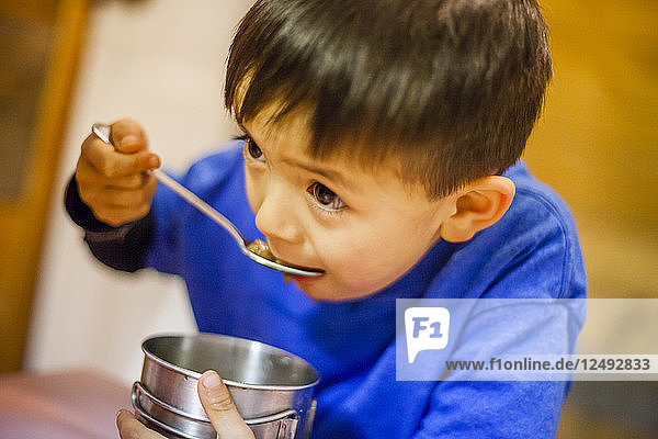 A 4 year old Japanese American boy eats from a metal mug.