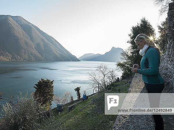 Woman uses digital tablet on promentory above lake