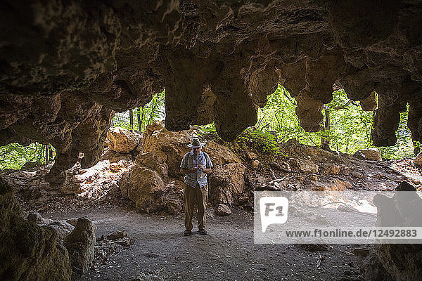 Older Gentleman Standing At The Mouth Of A Cave With Stalactites Hanging From The Ceiling