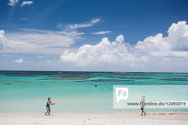 A man and woman throw a football on the white sand beach of the Caribbean's Anegada Island.