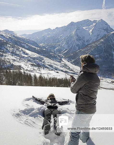 Mature man takes photo of woman making snow angel
