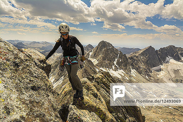 A woman rock climbing the SE ridge of West Twin Peak in Titcomb Basin  Wind River Range  Bridger Teton National Forest  Pinedale  Wyoming.