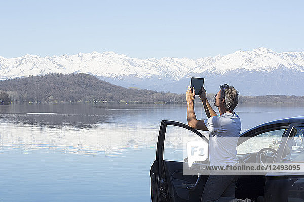 Mature man take photo of lake with tablet