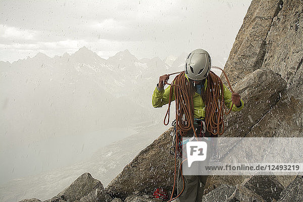 A woman coiling a rope in a summer snow storm while making a hasty retreat from the Red Tower Arete  Titcomb Basin  Wind River Range  Bridger Teton National Forest  Pinedale  Wyoming.