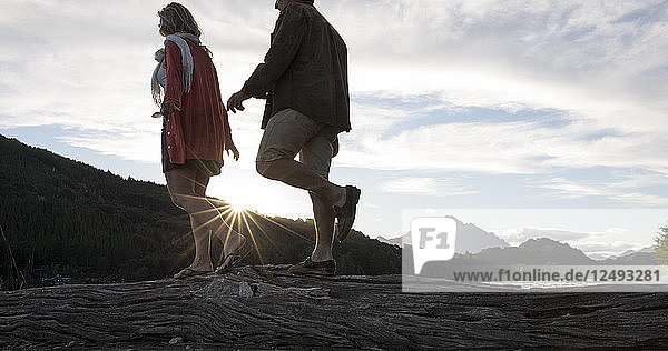 Mature couple balance along log together at sunset on lake