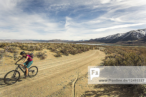 A young woman rides a mountain bike down a curving dirt road with mountains in the distance.