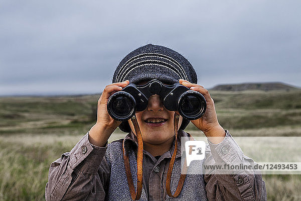 A 4 year old Japanese American boy dressed as an explorer with a hat and vest surveys the land (grasslands and prairies) with his binoculars in Badlands National Park  South Dakota.