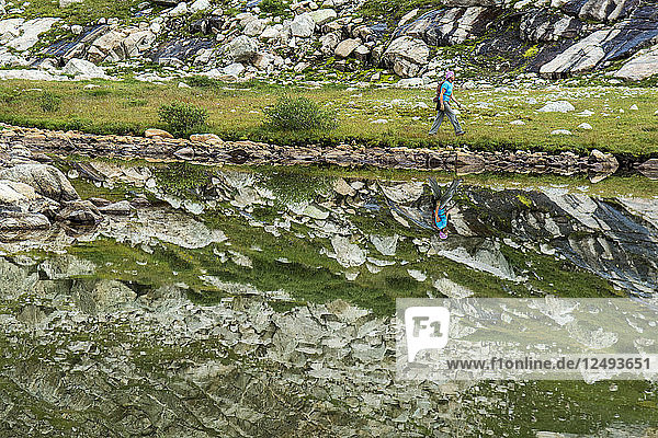 A woman hiking along edge of lake with granite reflections in Titcomb Basin in the Wind River Range  Bridger Teton National Forest  Pinedale  Wyoming.