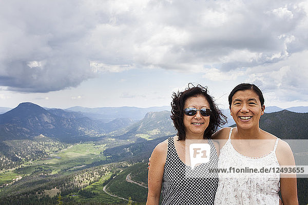 A Japanese American Mother and Daughter stand at Rainbow Curve Overview  with Rocky Mountain National Park stretching out behind them.